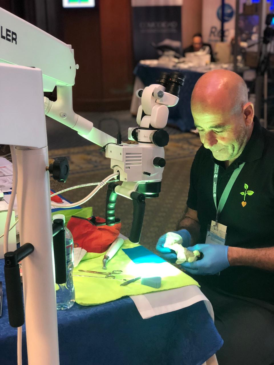 Dr. Sergio Rosler works in Seiler's booth using a microscope